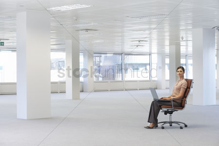 Interior : Woman using laptop in empty office space