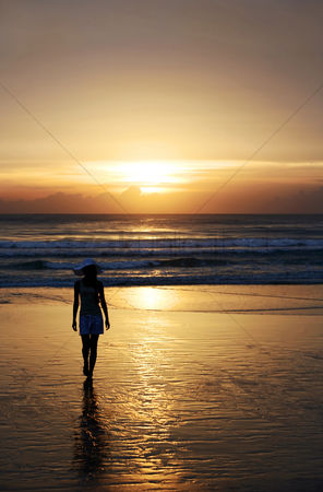 Background : Woman with hat walking on the beach