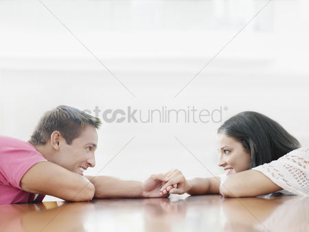 Romantic : Young couple holding hands across table and looking into each other s eyes