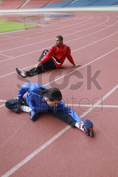 athletes warming up on running track stock photo