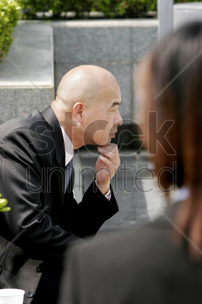 bald businessman sitting on the bench thinking stock photo
