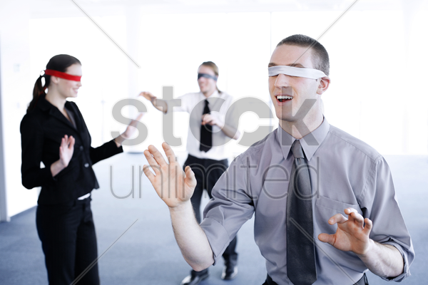 blindfolded business people finding their ways stock photo