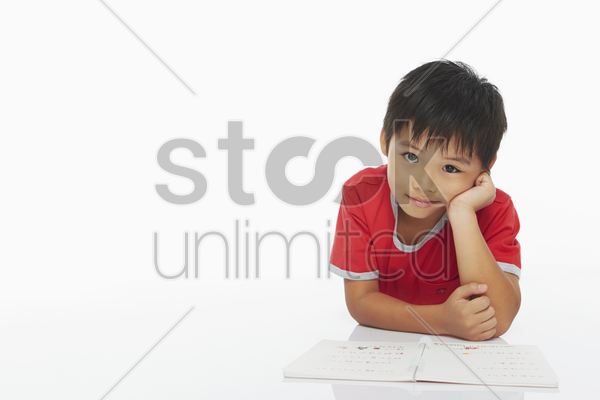 boy lying on his front, studying stock photo