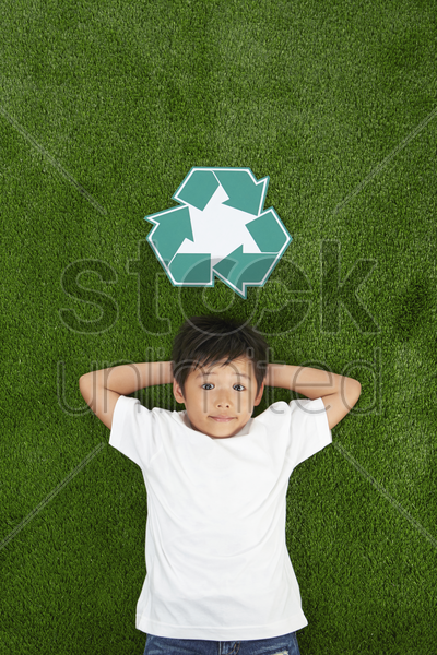 boy lying on the grass, smiling stock photo