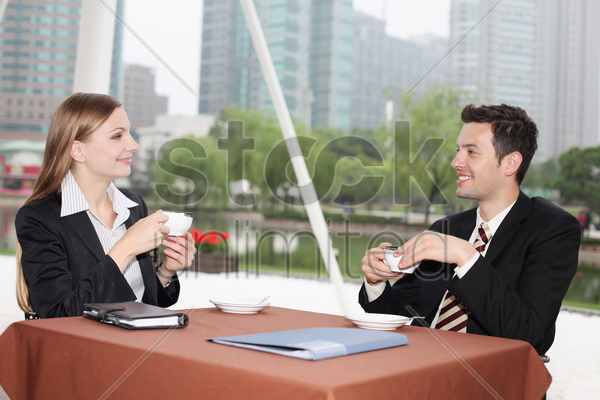 business people enjoying coffee at outdoor cafe stock photo