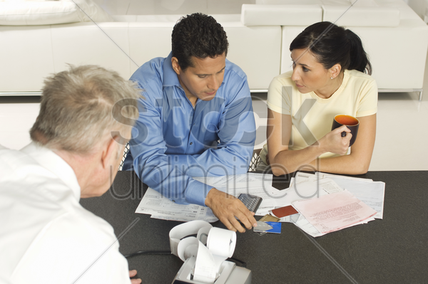 businessman assisting couple with credit cards stock photo