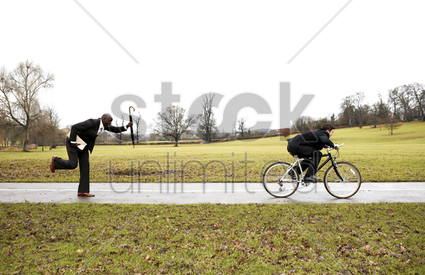 businessman chasing after another businessman stock photo