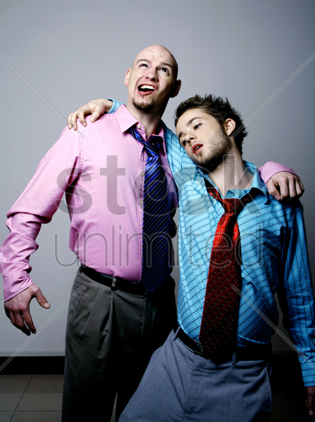 businessman helping his drunken colleague stock photo