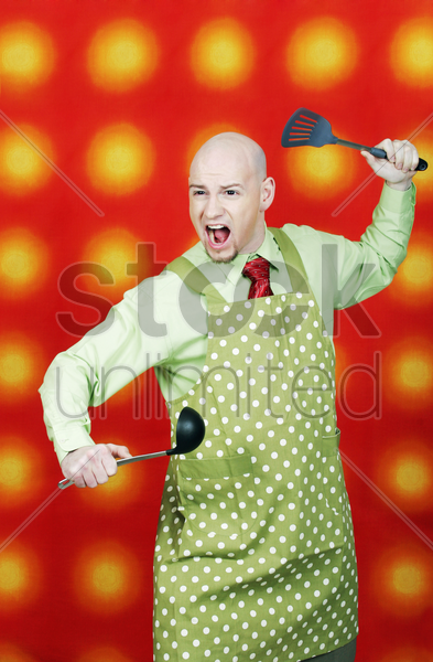 businessman in apron holding spatula and ladle stock photo