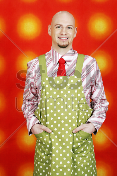 businessman in apron with his hands in pockets stock photo