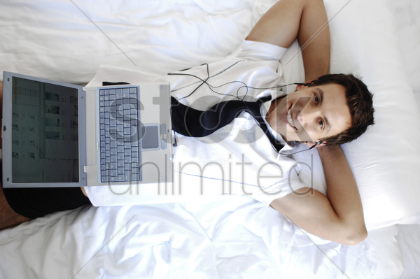 businessman listening to music on his earphones while using laptop stock photo