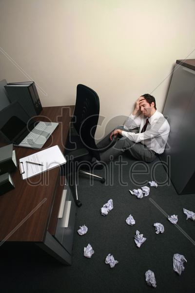 businessman sitting and crying, crumpled papers scattered on the floor stock photo