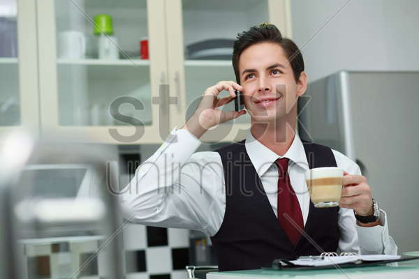 businessman talking on the phone while drinking coffee stock photo