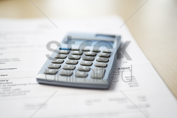 calculator lying on telephone bill close-up stock photo