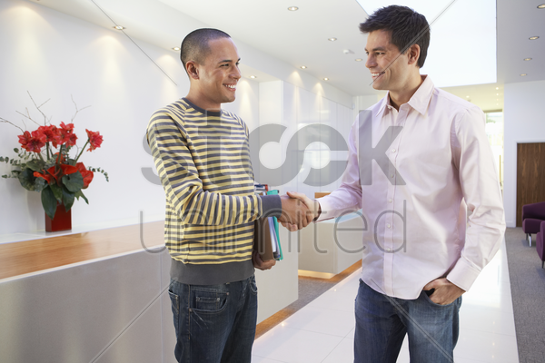 casually dressed businessmen smiling shaking hands in office stock photo