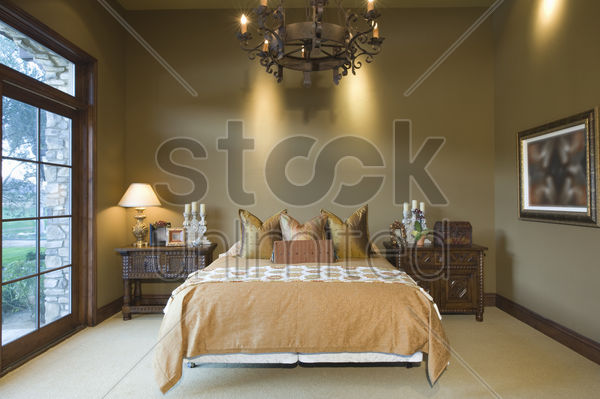 chandelier hangs over bed in palm springs home stock photo