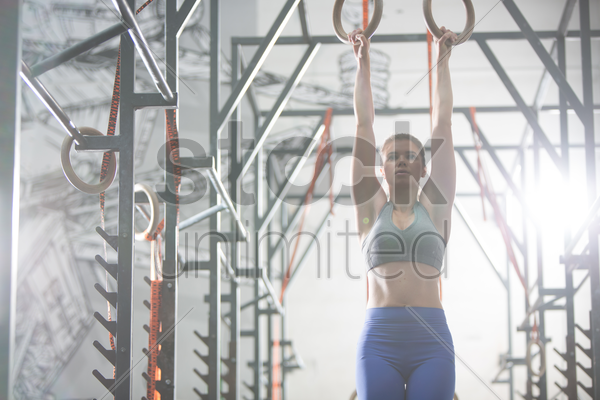 confident woman exercising with gymnastic rings in crossfit gym stock photo