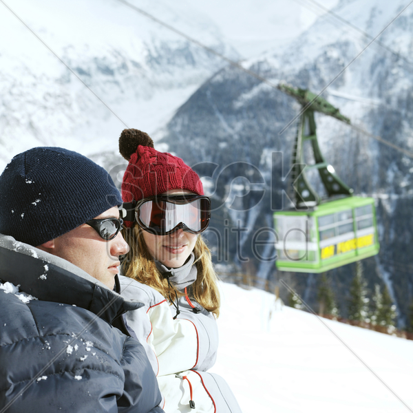 couple in warm clothing and ski goggles with cable car in the background stock photo