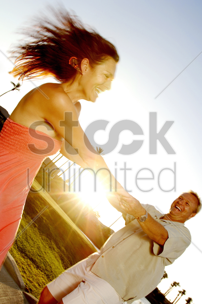 couple swinging each other around stock photo
