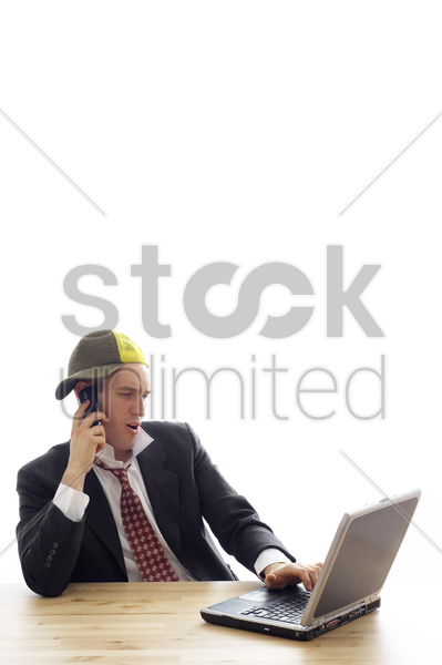 fashionable businessman talking on the cell phone while using laptop stock photo