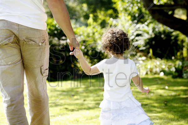 father and daughter holding hands while walking in the park stock photo