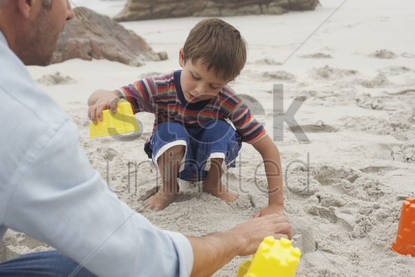 father playing with son on beach stock photo