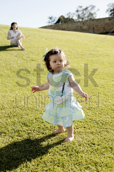 girl walking with her mother sitting in the background stock photo