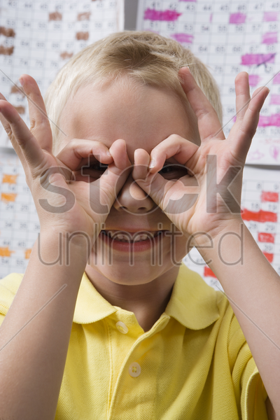 little boy making binoculars with his hands stock photo