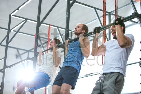low angle view of dedicated men doing chin-ups in crossfit gym stock photo