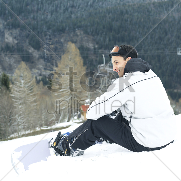 male snowboarder smiling while looking away stock photo
