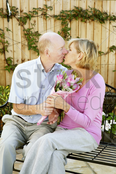 man and woman kissing while holding a bouquet of flowers stock photo