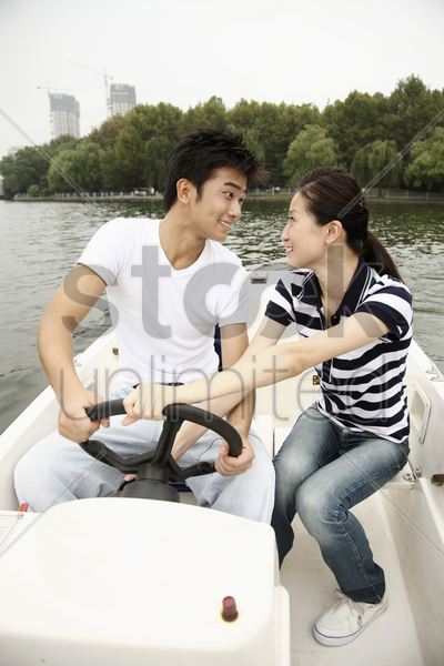 man and woman traveling on the boat stock photo