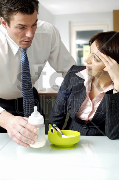 man passing a milk bottle to his wife stock photo