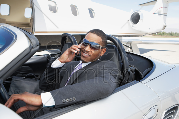 man sitting in convertible near private jet talking on mobile stock photo