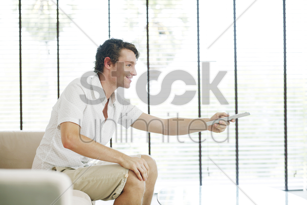 man sitting on the couch holding a television remote control stock photo
