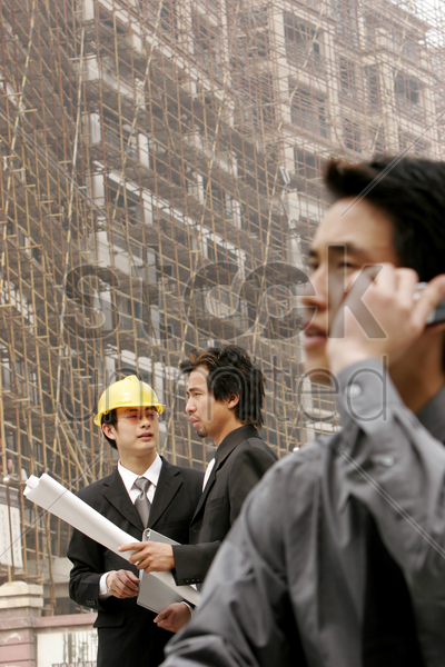 man talking on the hand phone while his colleague talking to the architect stock photo