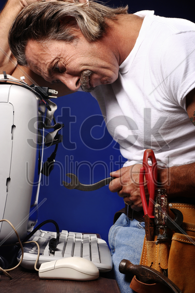 man trying to fix his computer stock photo