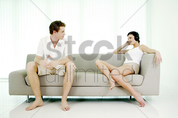 man watching woman listening to music on the headphones stock photo