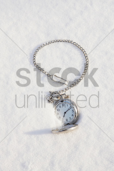 pocket watch in snow stock photo