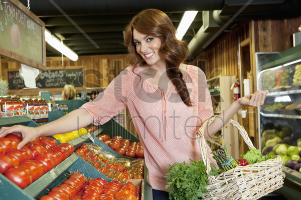 portrait of a happy brunette shopping for tomatoes in supermarket stock photo