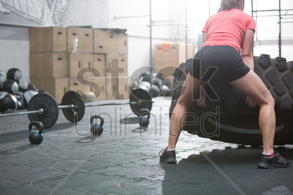 rear view of woman flipping tire in crossfit gym stock photo