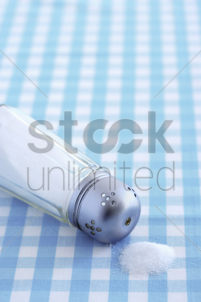 salt container lying on table with checked tablecloth stock photo