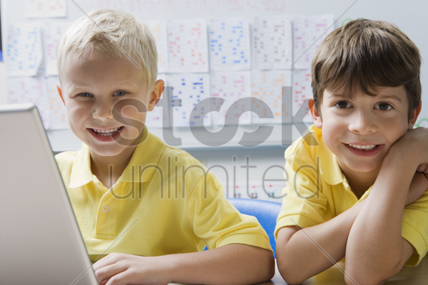 schoolboys using a laptop stock photo