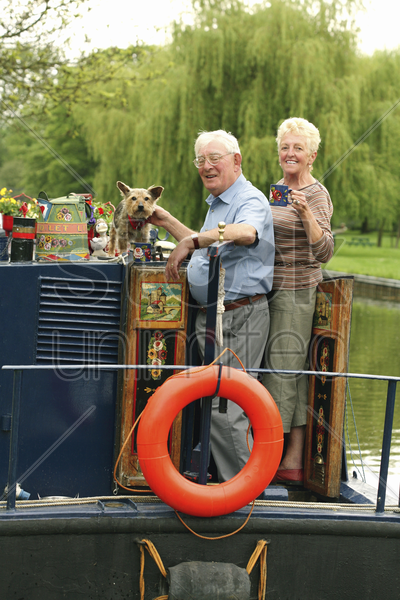 senior couple and their dog posing on the houseboat stock photo