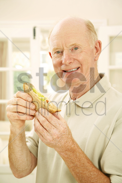senior man holding a sandwich stock photo