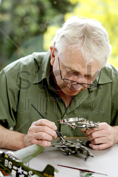 senior man painting model airplane stock photo
