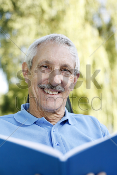 senior man smiling at the camera while holding a book stock photo