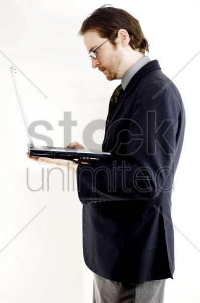 side shot of a bespectacled man in business suit placing a laptop on his palm stock photo