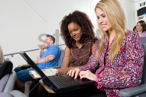 students using laptop in classroom stock photo