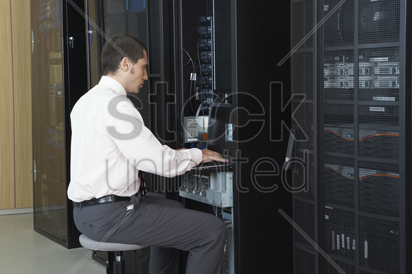 technician working in server room stock photo